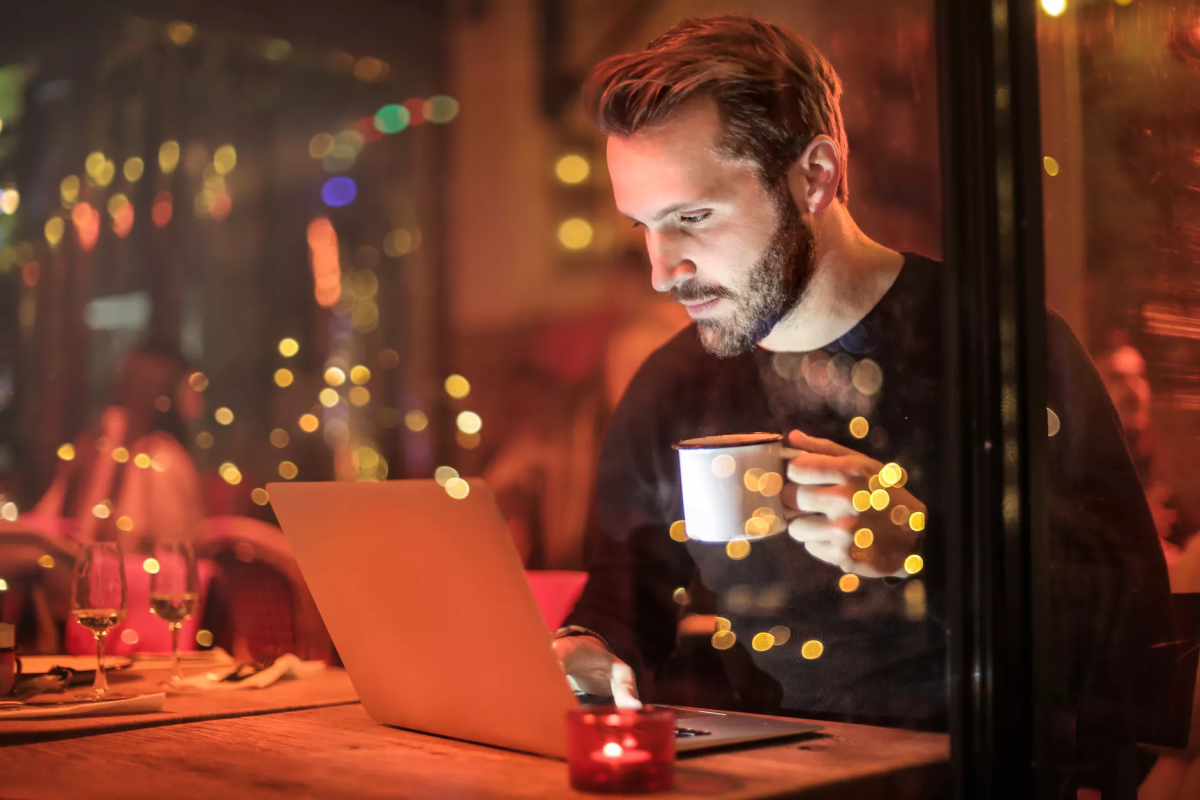 Man in coffee show with laptop using the RightLine Report, learning to trade stocks online.
