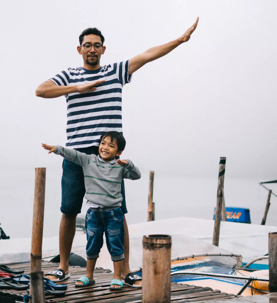 Image of tall father with a short son plays idea that shorting stocks online is really quite simple.